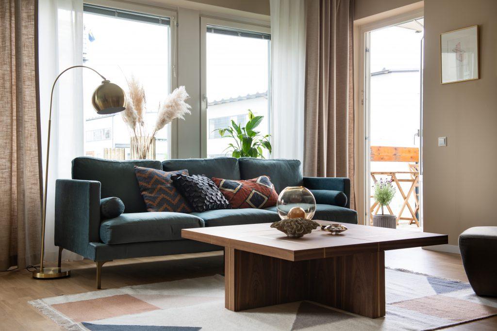 Soffa i sammet, kuddar, golvlampa i mässing, soffbord i valnöt, textilier. Mjuka toner.